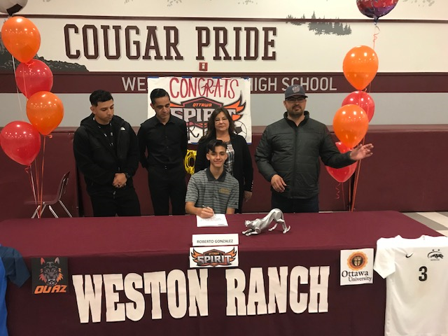 Flanked+by+his+parents+and+coaches%2C+Robert+Gonzalez+signs+his+letter.